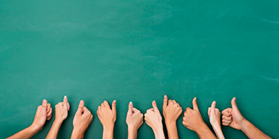 Close-up-view-of-the-hands-of-a-group-of-people-giving-a-thumbs-up-gesture-of-approval-an-success-with-their-hands-raised-against-a-blank-green-chalkboard-with-copyspace